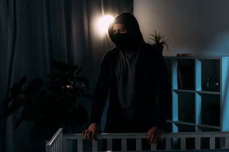 Pensive kidnapper in mask standing near crib and looking away Stock Photo