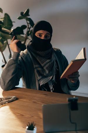 Terrorist in black mask holding gun and reading book