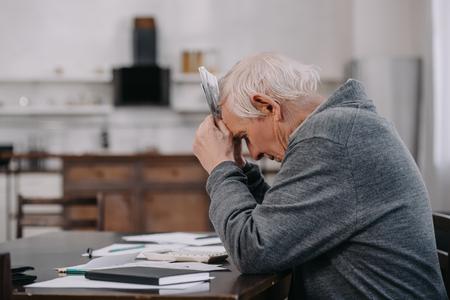zestresowany starszy mężczyzna w zwykłych ubraniach siedzi przy stole z papierkową robotą i trzyma pieniądze w domu