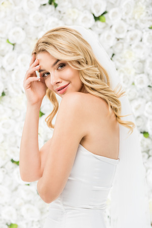 smiling beautiful bride posing at camera on white floral background