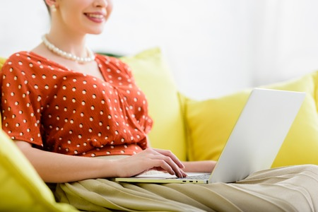 cropped view of smiling young woman in pearl necklace sitting on yellow sofa and using laptop