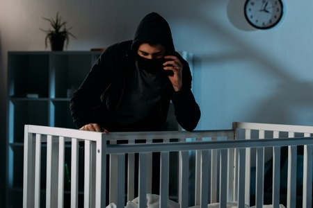 Kidnapper in mask talking on smartphone and looking in crib