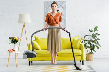 elegant barefoot young woman levitating in air and holding vacuum cleaner