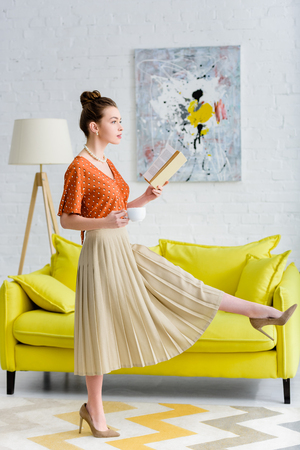 elegant young woman holding book and coffee cup while marching in living room