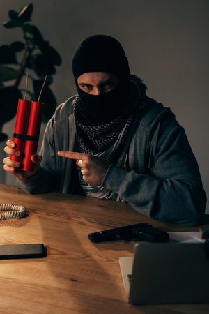 Angry terrorist in mask pointing with finger at dynamite in room