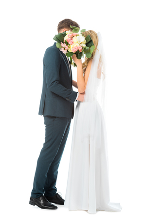 bride in long wedding dress, and groom in elegant suit embracing while hiding faces behind wedding bouquet isolated on white