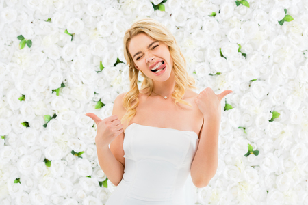 excited young woman showing thumbs up and funny grimacing on white floral background Stock Photo
