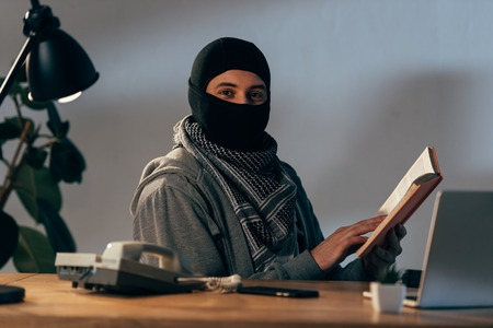 Terrorist in black mask sitting at table and reading book