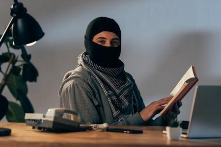 Terroriste en masque noir assis à table et livre de lecture