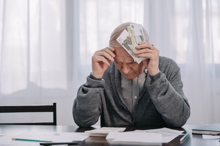 stressed senior man sitting at table with paperwork and holding money at home