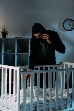 Criminal in mask talking on smartphone while kidnapping child Stock Photo