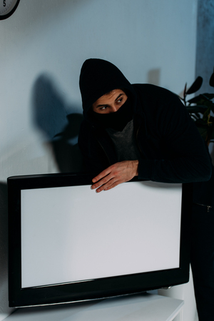 Suspicious thief in mask stealing flat-screen tv with blank screen Stock Photo