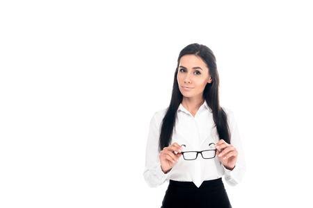 Interested businesswoman in formal wear holding glasses isolated on white