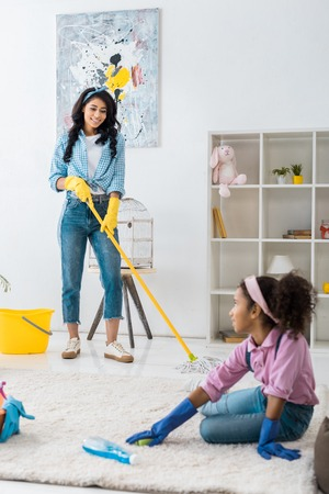 cute african american child cleaning carpet while mother washing floor