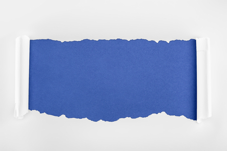ragged textured white paper with curl edges on blue background