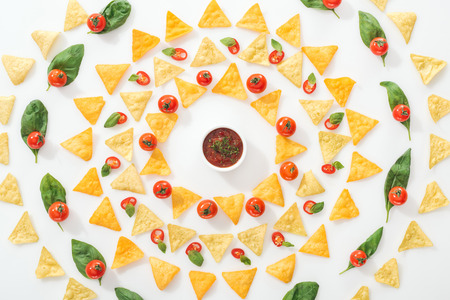 flat lay with tasty nachos, sauce and sliced chili peppers with basil and cherry tomatoes on white background