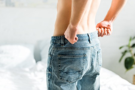 cropped view of man with bare torso standing and putting on blue jeans at home Stock Photo