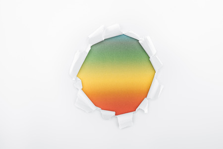 ragged hole in white paper on multicolored background