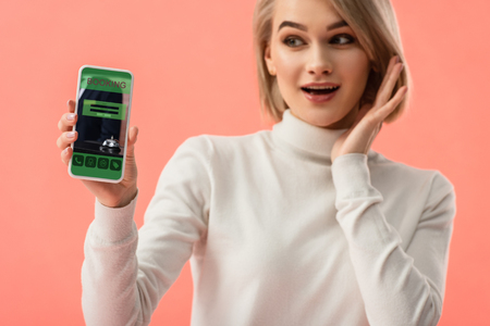selective focus of surprised blonde woman holding smartphone with booking app on screen isolated on pink Stok Fotoğraf