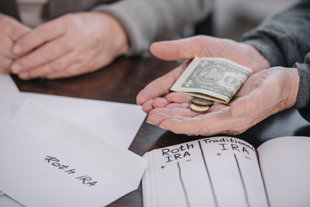 cropped view of couple holding money near envelope with roth ira lettering and notebook Stock Photo