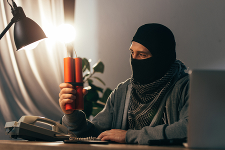 Terrorist in mask looking at lighted dynamite in room