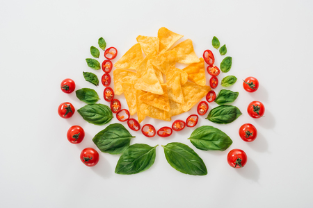 flat lay with nachos, cut chili peppers, basil leaves and ripe cherry tomatoes Stock Photo
