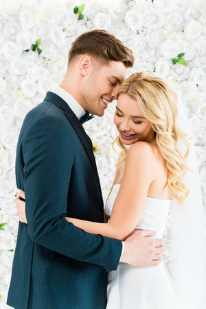 happy beautiful bride hugging smiling groom on white floral background