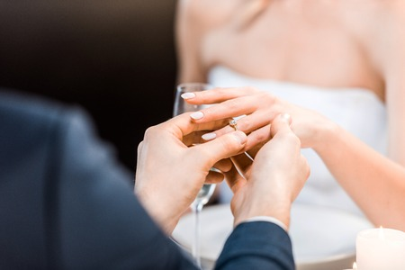 selective focus of man putting wedding ring on brides finger on black background 스톡 콘텐츠