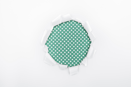 torn hole in white textured paper on green dotted background Banque d'images - 120413204