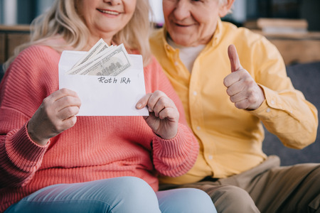 cropped view of senior couple showing thumb up sign while holding envelope with roth ira lettering and dollar banknotes