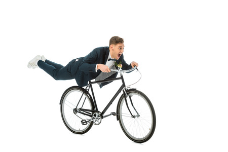 excited groom in elegant suit making stunts on bike isolated on white