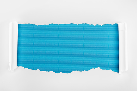ripped white paper with rolled edges on blue striped background Imagens