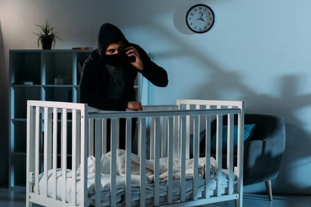 Kidnapper in black mask standing near crib and talking on smartphone Stock Photo