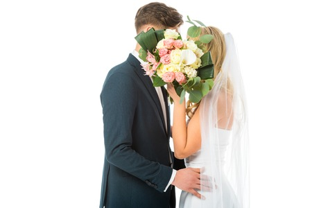 bride and groom hugging while hiding faces behind wedding bouquet isolated on white Stock Photo