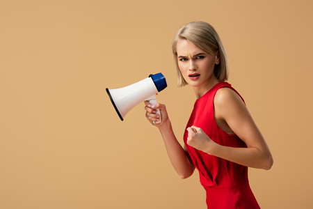irritated woman in red dress holding megaphone isolated on beige