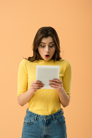 Shocked brunette young woman looking at digital tablet isolated on orange