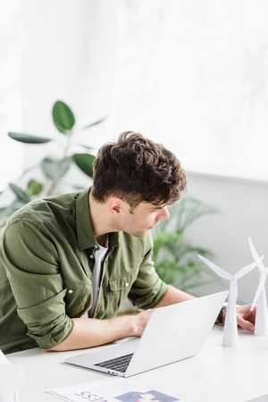handsome architect sitting at table with laptop and putting windmill models in office