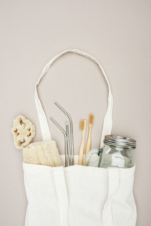 bamboo toothbrushes, organic loofah, jar and stainless steel straws in white cotton bag on grey background