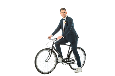 cheerful handsome bridegroom in elegant suit and sneakers sitting on bike isolated on white Stock Photo - 120412729