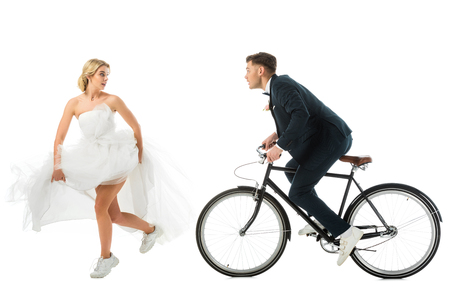 attractive bride in wedding dress and sneakers running from groom on bicycle isolated on white