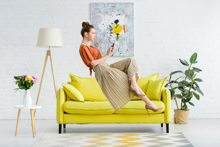 elegant young woman levitating in air and using digital tablet in living room Stok Fotoğraf
