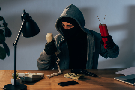 Angry terrorist in mask with dynamite sitting in room and holding handset Stock Photo