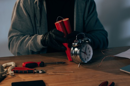 Cropped view of criminal in leather gloves making bomb Stock Photo
