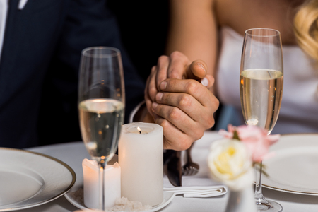 selective focus of man and woman holding hands while sitting at served table on black background