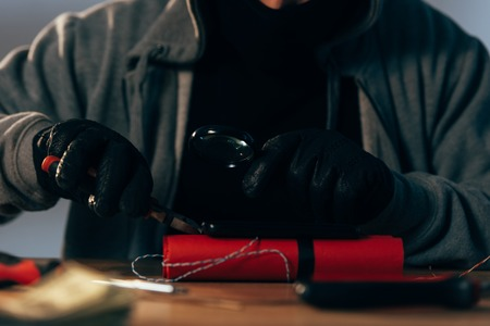 Partial view of terrorist in leather gloves making bomb Stock Photo