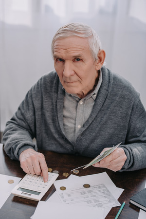 senior man sitting at table with paperwork, using calculator while counting money and looking at camera