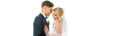 handsome bridegroom talking to beautiful smiling bride isolated on white