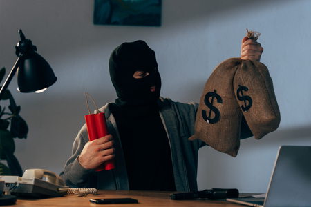 Terrorist in mask holding dynamite and looking at money bags in room