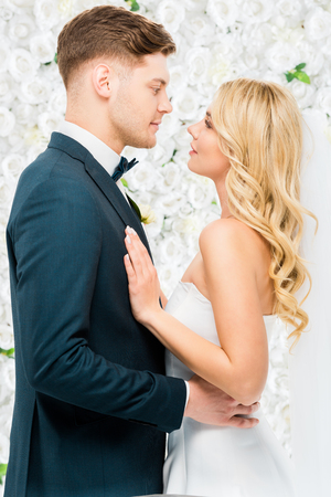 happy young bride and groom standing face to face on white floral background