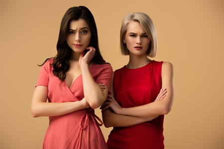 upset beautiful women in red dresses with crossed arms looking at camera isolated on beige